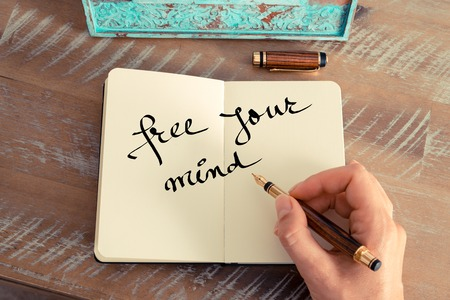 free your mind: Retro effect and toned image of a woman hand writing a note with a fountain pen on a notebook. Motivational concept with handwritten text FREE YOUR MIND