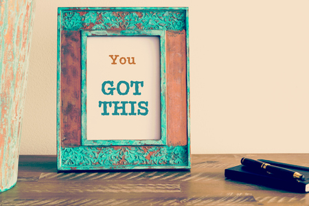Retro effect and toned image of a vintage photo frame next to fountain pen and notebook . Motivational quote written with typewriter font YOU GOT THIS Zdjęcie Seryjne