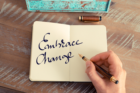 Retro effect and toned image of a woman hand writing a note with a fountain pen on a notebook. Motivational concept with handwritten text EMBRACE CHANGE Stock Photo