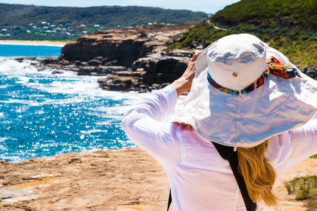 turn away: Young woman with hat looking away, ocean background