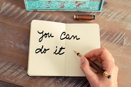 tu puedes: efecto retro y la imagen en tonos de la mano de una mujer que escribe una nota con una pluma en un cuaderno. Concepto de motivación con el texto escrito a mano USTED PUEDE HACERLO Foto de archivo