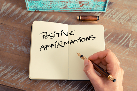 Retro effect and toned image of a woman hand writing a note with a fountain pen on a notebook. Motivational concept with handwritten text POSITIVE AFFIRMATIONS Banque d'images