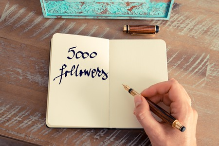 followers: Retro effect and toned image of a woman hand writing a note with a fountain pen on a notebook. Motivational concept with handwritten text 5000 FOLLOWERS