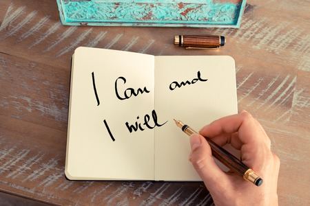 Retro effect and toned image of a woman hand writing a note with a fountain pen on a notebook. Motivational concept with handwritten text I CAN AND I WILL