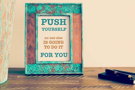 Retro effect and toned image of a vintage photo frame next to fountain pen and notebook . Motivational quote written with typewriter font PUSH YOURSELF NO ONE ELSE IS GOING TO DO IT FOR YOU