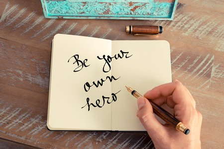 Retro effect and toned image of a woman hand writing a note with a fountain pen on a notebook. Motivational concept with handwritten text BE YOUR OWN HERO Stock Photo