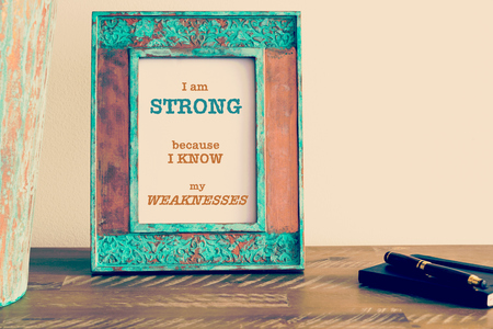 weaknesses: Retro effect and toned image of a vintage photo frame next to fountain pen and notebook . Motivational quote written with typewriter font I AM STRONG BECAUSE I KNOW MY WEAKNESSES