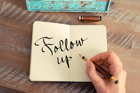 Retro effect and toned image of a woman hand writing a note with a fountain pen on a notebook. Motivational concept with handwritten text FOLLOW UP