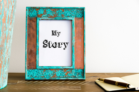 photo story: Vintage photo frame on wooden table over white wall background with motivational message MY STORY , copy space available