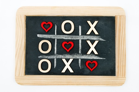 replaced: Vintage chalkboard with Tic Tac Toe Game Competition XO Win created of wood letters and red hearts, letters O and X replaced with red heart shapes, isolated on white, Love Always Wins Concept Stock Photo