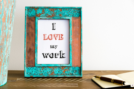 Vintage photo frame on wooden table over white wall background with motivational message I LOVE MY WORK, copy space available