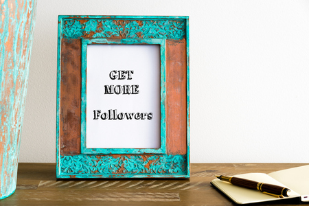 Vintage photo frame on wooden table over white wall background with motivational message GET MORE FOLLOWERS , copy space available