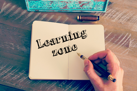 self improvement: Retro effect and toned image of a woman hand writing a note with a fountain pen on a notebook. Motivational message LEARNING ZONE as concept for self improvement