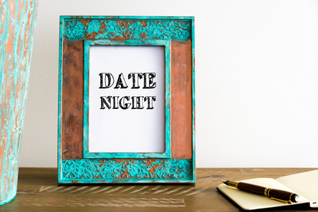 date night: Vintage photo frame on wooden table over white wall background with motivational message DATE NIGHT , copy space available