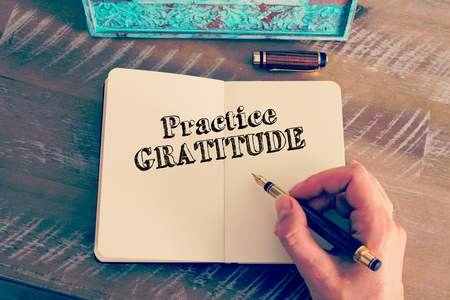Retro effect and toned image of a woman hand writing a note with a fountain pen on a notebook. Motivational message PRACTICE GRATITUDE as concept for self improvement Banque d'images