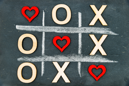 replaced: Vintage chalkboard with Tic Tac Toe Game Competition XO Win created of wood letters and red hearts, letters O and X replaced with red heart shapes, Challenge and Love Always Wins Concept