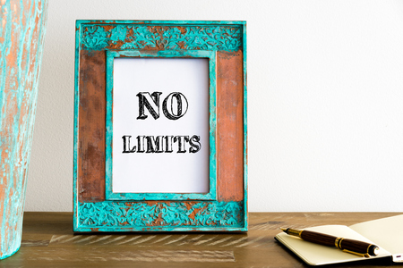 no limits: Vintage photo frame on wooden table over white wall background with motivational message NO LIMITS , copy space available Stock Photo