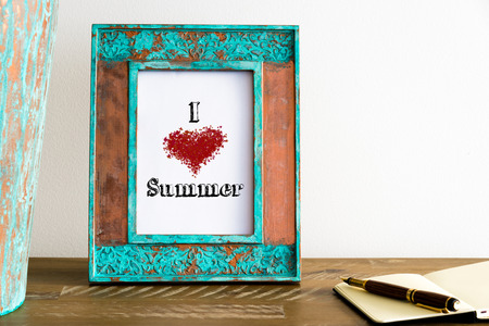 Vintage photo frame on wooden table over white wall background with motivational message I LOVE SUMMER , copy space available