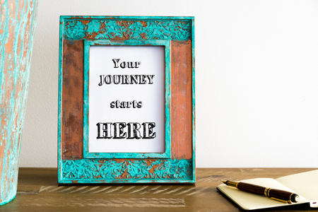 Vintage photo frame on wooden table over white wall background with motivational message YOUR JOURNEY STARTS HERE , copy space available
