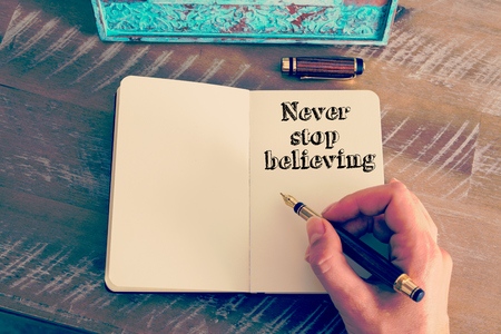 believing: Retro effect and toned image of a woman hand writing a note with a fountain pen on a notebook. Motivational message NEVER STOP BELIEVING as concept for self improvement