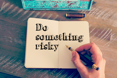 risky: Retro effect and toned image of a woman hand writing a note with a fountain pen on a notebook. Motivational message DO SOMETHING RISKY as concept for self improvement