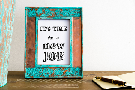 available time: Vintage photo frame on wooden table over white wall background with motivational message ITS TIME FOR A NEW JOB, copy space available Stock Photo