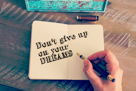 self improvement: Retro effect and toned image of a woman hand writing a note with a fountain pen on a notebook. Motivational message DONT GIVE UP ON YOUR DREAMS as concept for self improvement