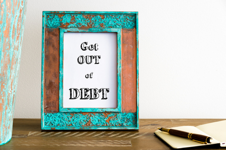 get out: Vintage photo frame on wooden table over white wall background with motivational message GET OUT OF DEBT , copy space available