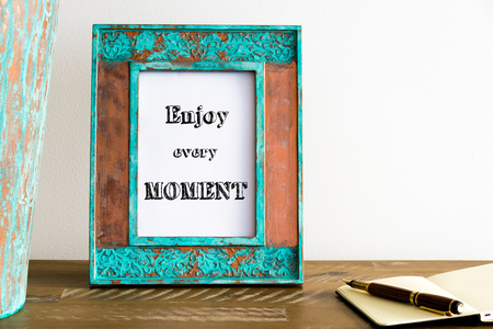 enjoy space: Vintage photo frame on wooden table over white wall background with motivational message ENJOY EVERY MOMENT , copy space available