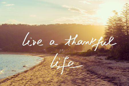 Handwritten text over sunset calm sunny beach background, LIVE A THANKFUL LIFE, vintage filter applied, motivational concept image Stock Photo