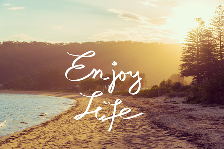 Handwritten text over sunset calm sunny beach background, ENJOY LIFE, vintage filter applied, motivational concept image