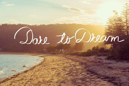 Handwritten text over sunset calm sunny beach background, DARE TO DREAM, vintage filter applied, motivational concept image