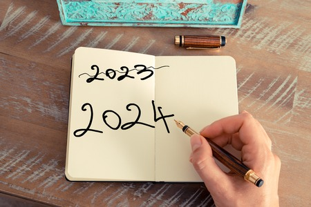 Retro effect and toned image of a woman hand writing a note with a fountain pen on a notebook. Motivational concept with Handwritten text Happy New Year 2024 and 2023 written off