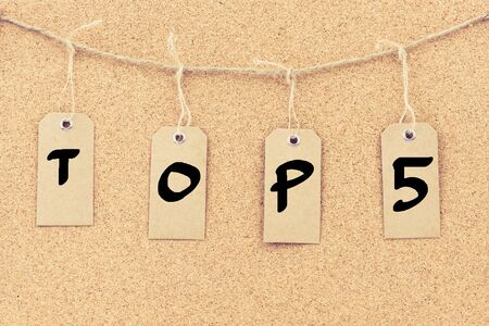 string top: Vintage grunge tags with letters on rope string, word TOP 5 over cork board texture background, filter applied, available copy space.