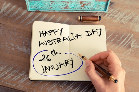 australia day: Retro effect and toned image of a woman hand writing a note with a fountain pen on a notebook. Concept image with handwritten text HAPPY AUSTRALIA DAY 26 JANUARY