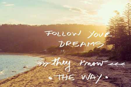 they: Handwritten text over sunset calm sunny beach background, FOLLOW YOUR DREAMS THEY KNOW THE WAY, vintage filter applied, motivational concept image