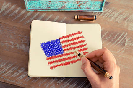 visions of america: Retro effect and toned image of a woman hand drawing the American Flag with a fountain pen on a notebook. Concept image with hand drawing of United States of America flag