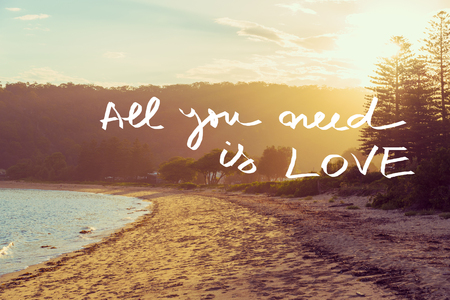 all weather: Handwritten text over sunset calm sunny beach background, ALL YOU NEED IS LOVE, vintage filter applied, motivational concept image Stock Photo