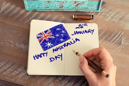 jornada de trabajo: efecto retro y la imagen en tonos de la mano de una mujer que escribe una nota con una pluma en un cuaderno. Concepto de imagen con texto escrito a mano FELIZ DÍA DE AUSTRALIA 26 de enero y el indicador australiano