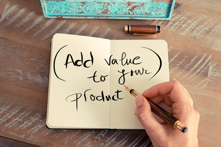 value add: Retro effect and toned image of a woman hand writing a note with a fountain pen on a notebook. Handwritten text ADD VALUE TO YOUR PRODUCT, business success concept
