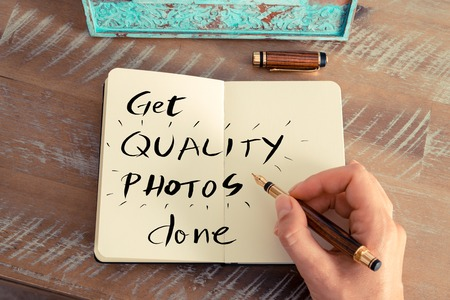 pen quality: Retro effect and toned image of a woman hand writing a note with a fountain pen on a notebook. Handwritten text GET QUALITY PHOTOS DONE, business success concept