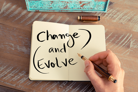 evolve: Retro effect and toned image of a woman hand writing a note with a fountain pen on a notebook. Handwritten text CHANGE AND EVOLVE, business success concept