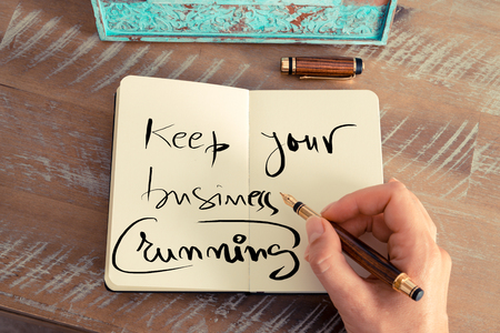 keep your hands: Retro effect and toned image of a woman hand writing a note with a fountain pen on a notebook. Handwritten text KEEP YOUR BUSINESS RUNNING, business success concept