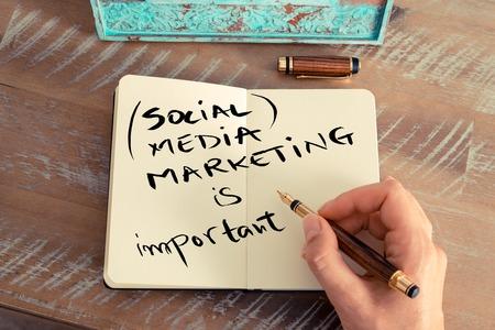 trabajo social: efecto retro y la imagen en tonos de la mano de una mujer que escribe una nota con una pluma en un cuaderno. texto escrito a mano SOCIAL MEDIA MARKETING ES IMPORTANTE, el concepto de éxito del negocio