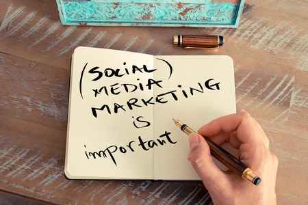 social media marketing: Retro effect and toned image of a woman hand writing a note with a fountain pen on a notebook. Handwritten text SOCIAL MEDIA MARKETING IS IMPORTANT, business success concept