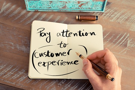 pay attention: Retro effect and toned image of a woman hand writing a note with a fountain pen on a notebook. Handwritten text PAY ATTENTION TO CUSTOMER EXPERIENCE, business success concept