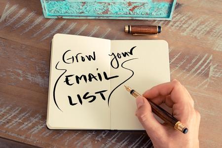 Retro-Effekt und getönten Bild einer Frau Hand eine Notiz mit einem Füllfederhalter auf einem Notebook zu schreiben. Handwritten Text Steigern Sie Ihre Email-Liste, geschäftlichen Erfolg Konzept