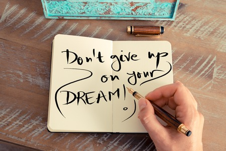 Retro effect and toned image of a woman hand writing a note with a fountain pen on a notebook. Handwritten text DONT GIVE UP ON YOUR DREAM, business success concept Stock Photo