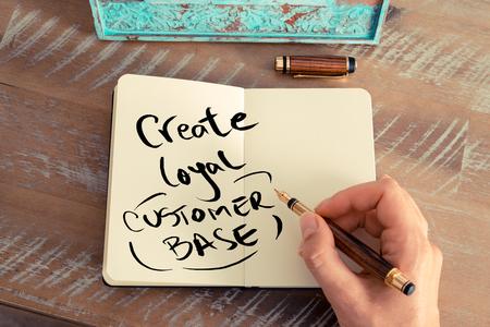 effet rétro et de l'image d'une femme tonique main d'écrire une note avec un stylo sur un ordinateur portable. texte Handwritten CREATE LOYAL BASE CLIENT, le concept de la réussite des entreprises