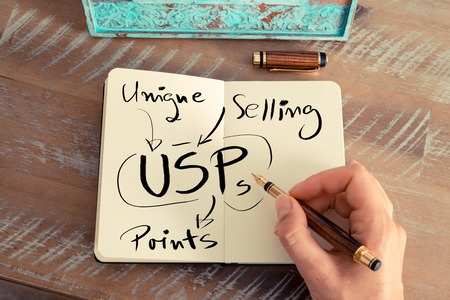 selling points: Retro effect and toned image of a woman hand writing a note with a fountain pen on a notebook. Handwritten text USP AS UNIQUE SELLING POINTS, business success concept Stock Photo